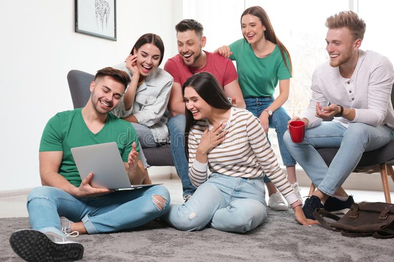 Group of happy people with laptop in room stock image