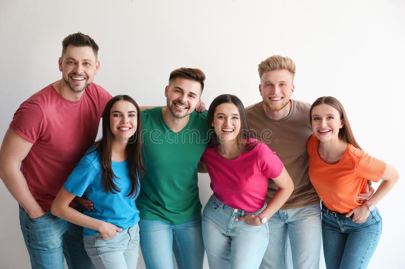 Group of happy people posing near wall stock photo