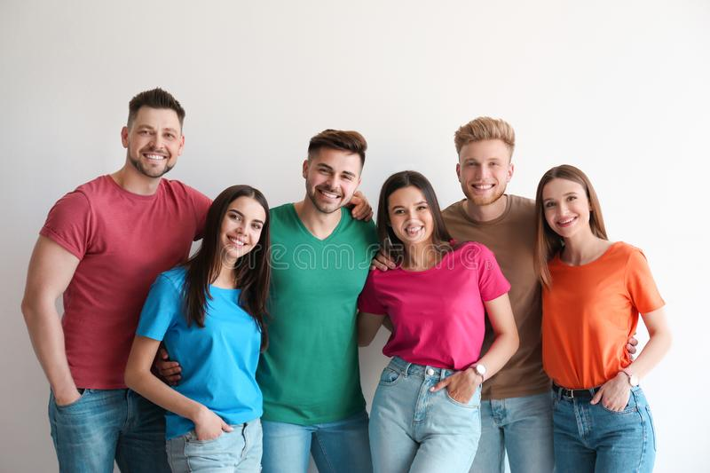 Group of happy people posing near wall stock image