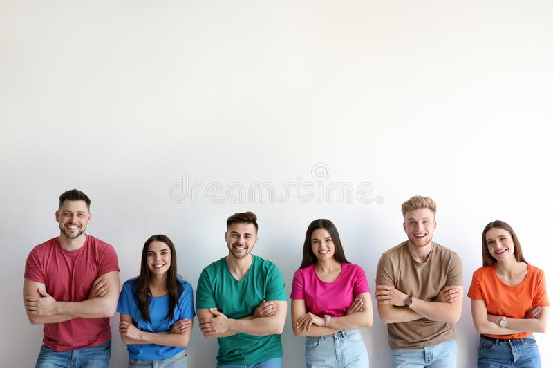 Group of happy people posing near light wall royalty free stock image