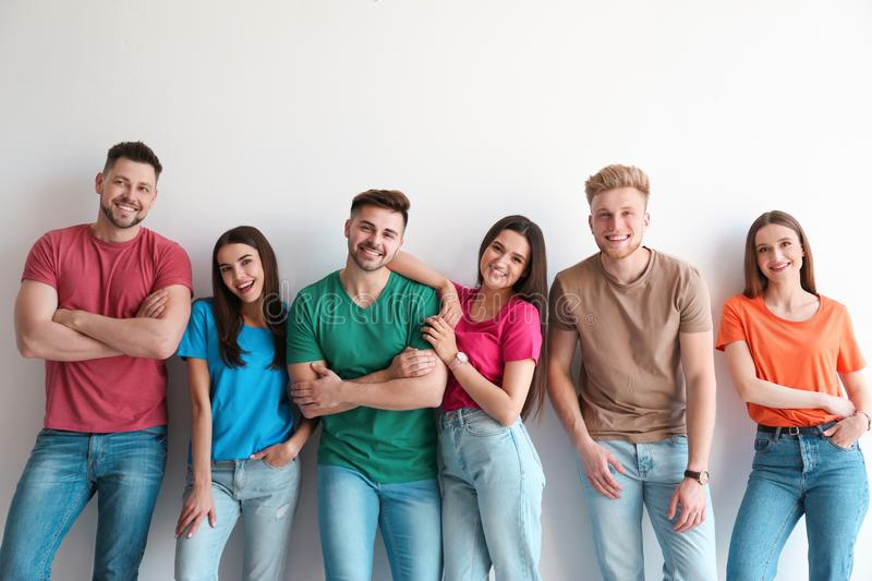Group of happy people posing near wall stock photos