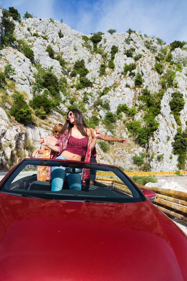 Group of happy people in red convertible car. royalty free stock image