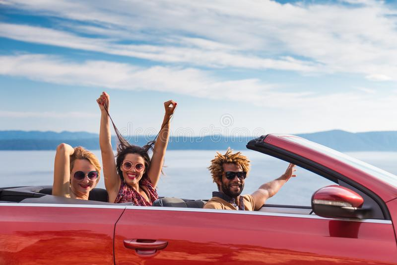 Group of happy people in red convertible car. royalty free stock photography