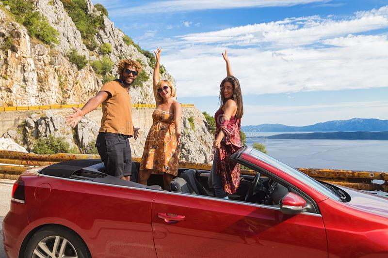 Group of happy people in red convertible car. stock photos