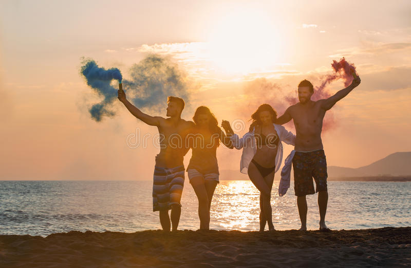 Group of happy people walking on beautiful beach in summer sunset royalty free stock photos