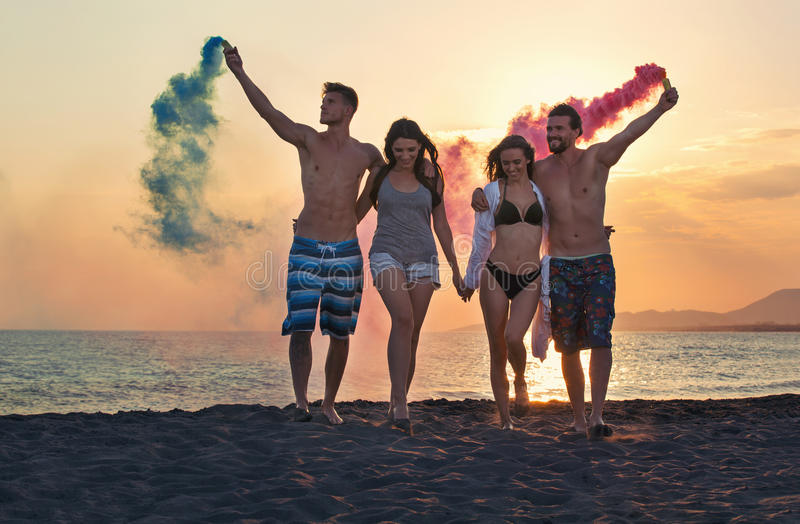 Group of happy people walking on beautiful beach in summer sunset stock image