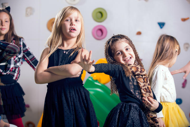 Group of happy preschoolers dancing in playroom stock images