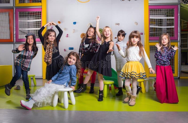 Group of happy preschoolers dancing in playroom stock photography