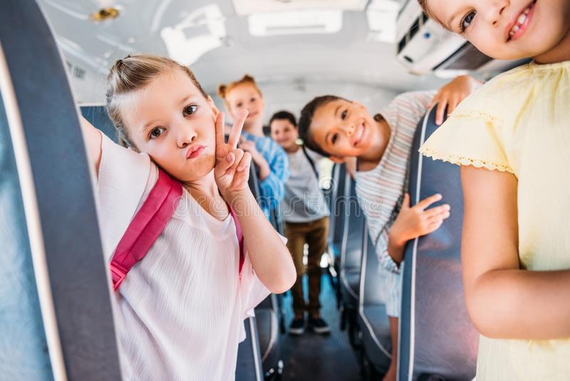 group of happy schoolchildren riding on school bus and looking royalty free stock photography
