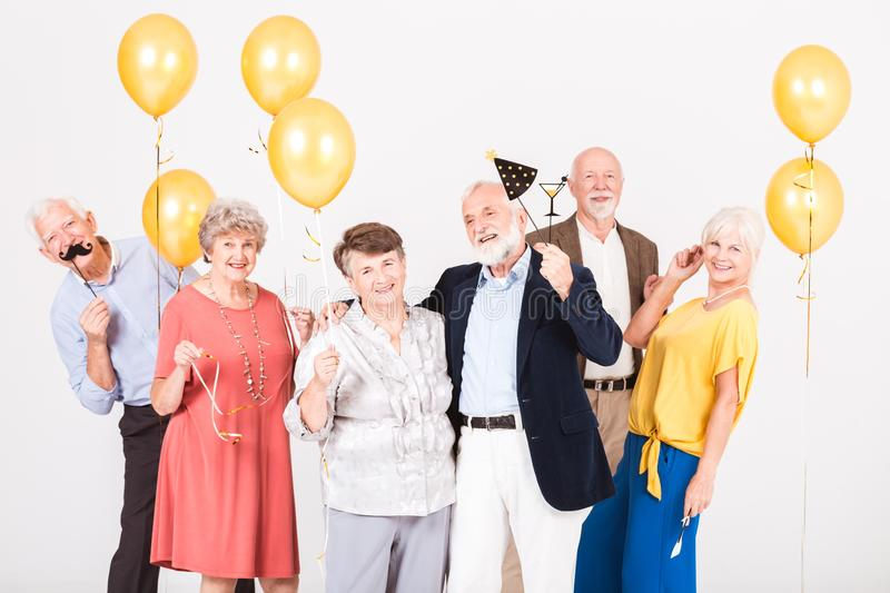 Group of happy senior friends holding balloons and standing in white interior stock photography