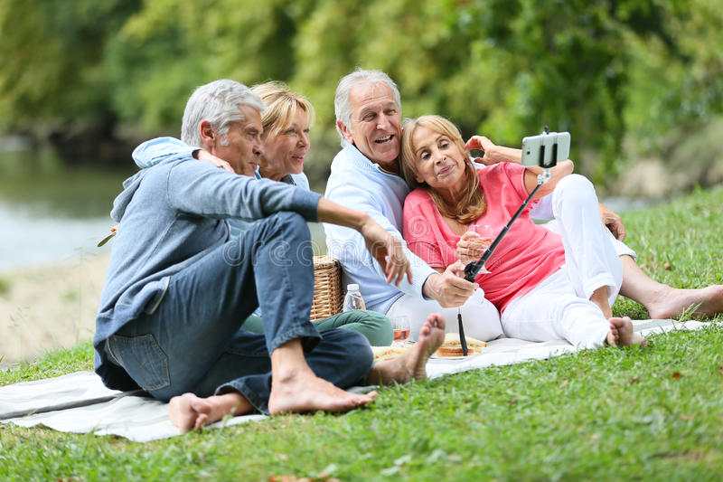 Group of happy seniors having pic-nic taking selfie souvenir stock image