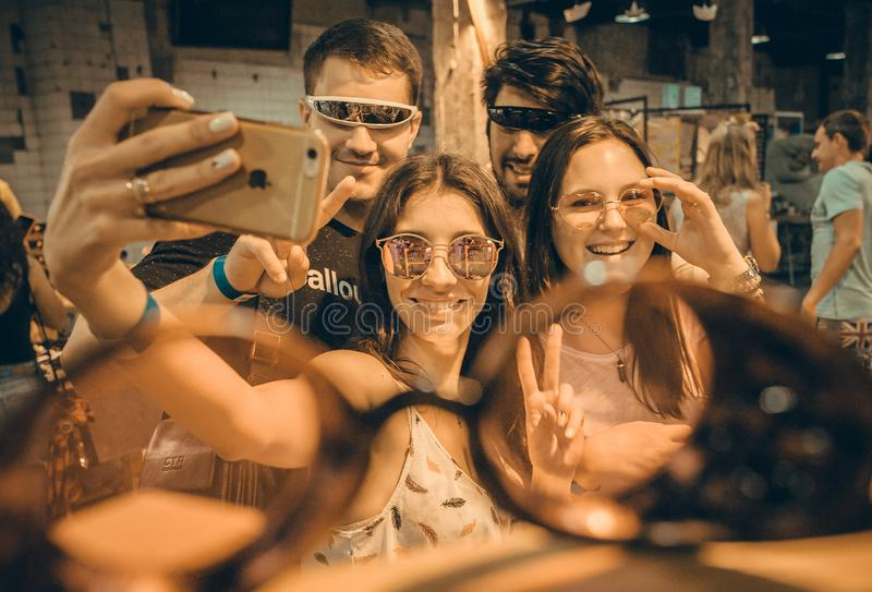 Group of happy and smiley young people making selfie inside sunglasses store stock photo
