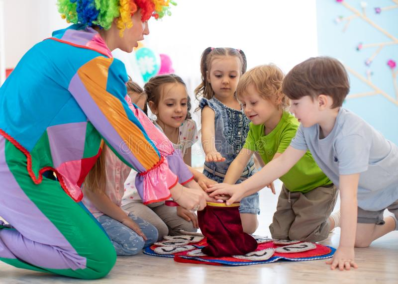 Group of happy smiling kids watching at clown show indoor. Party for children. stock images
