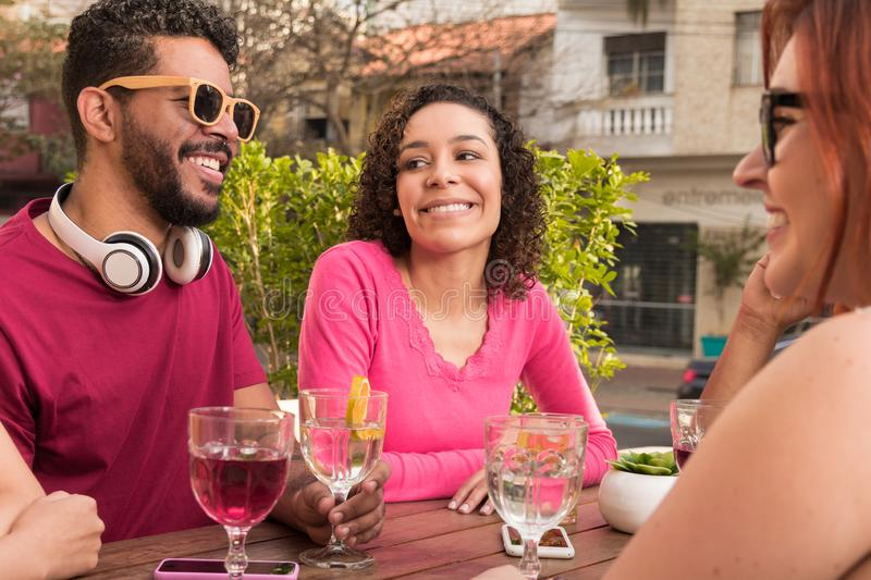 Diverse group of friends having fun at cafe bar outdoor. royalty free stock image