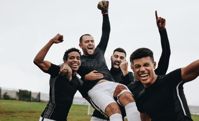 Group of happy soccer players celebrating a win by lifting their goalkeeper. Footballers celebrating victory by raising their hand. In air and screaming in stock images