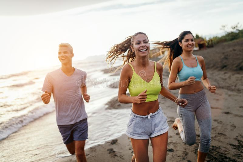 Group of sport people jogging on the beach royalty free stock images