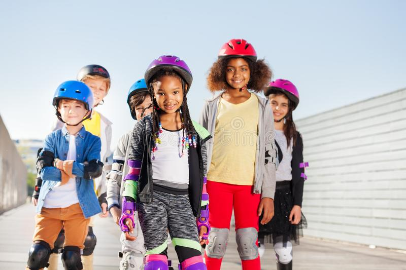 Group of happy sporty kids rollerblading outdoors. Group of happy sporty kids, preteen boys and girls in safety gear rollerblading outdoors royalty free stock images