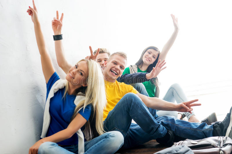 Group of happy students on a break waving. Focus on students. Background is blurry stock photos