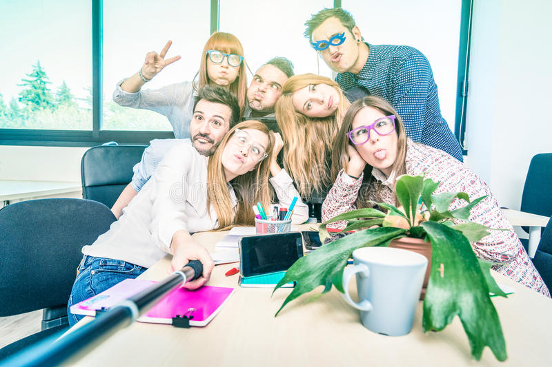 Group of happy students employee workers taking selfie. With stick - University business concept of human resource on working fun time - Start up entrepreneurs royalty free stock image