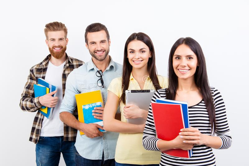 Group of happy students standing in a row and smiling in casualwear holding books. They like to study and enjoy to work in team. royalty free stock images