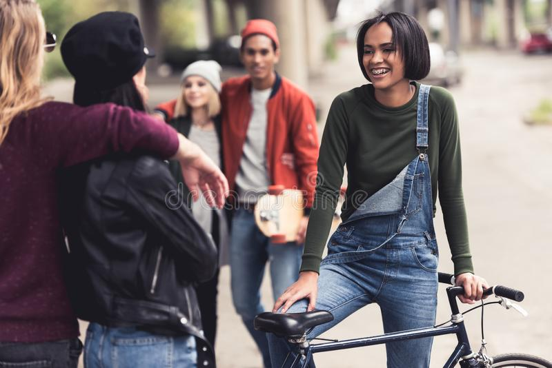 group of happy stylish people with vintage bike spending time royalty free stock photography