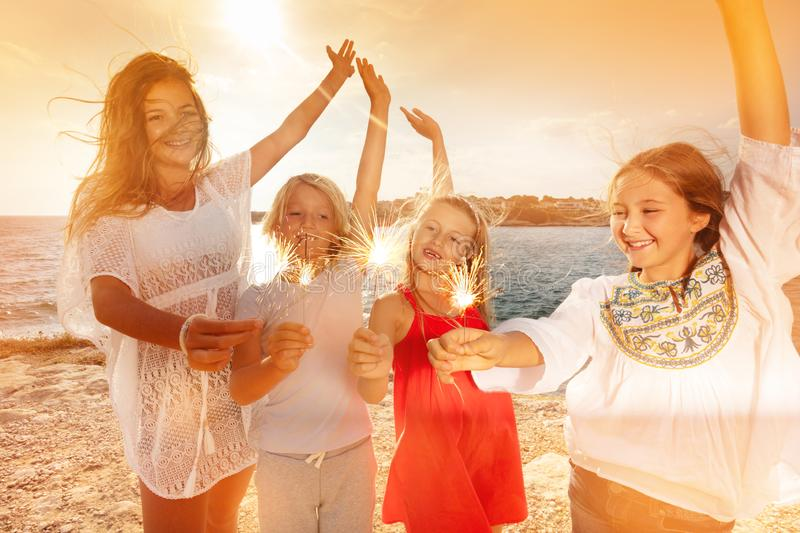 Teens having fun using sparklers on beach party royalty free stock photo