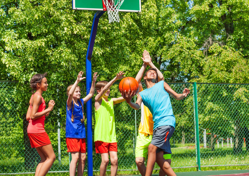 Group of happy teenagers playing basketball stock photo