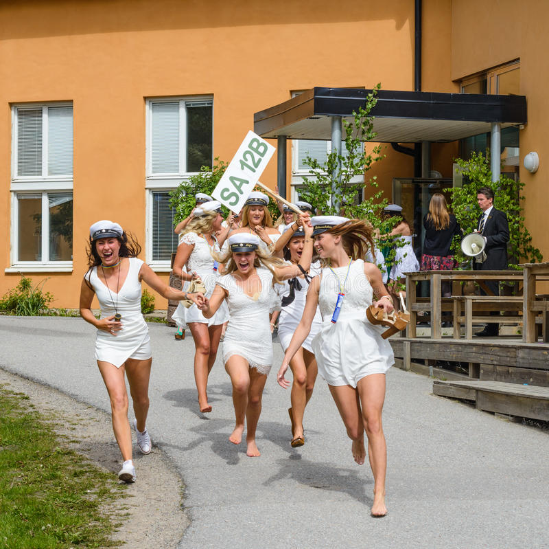 Group of happy teenagers wearing graduation caps running out from school after graduation from high school at the school. Stockholm, Sweden - June 5, 2015: Group stock photography