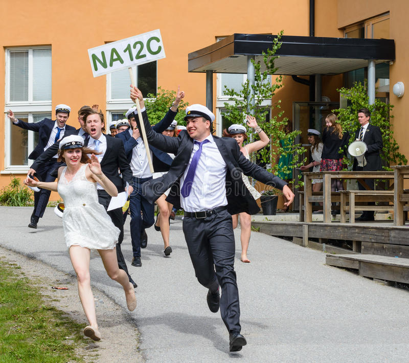 Group of happy teenagers wearing graduation caps running out from school after graduation from high school at the school. SStockholm, Sweden - June 5, 2015 stock images