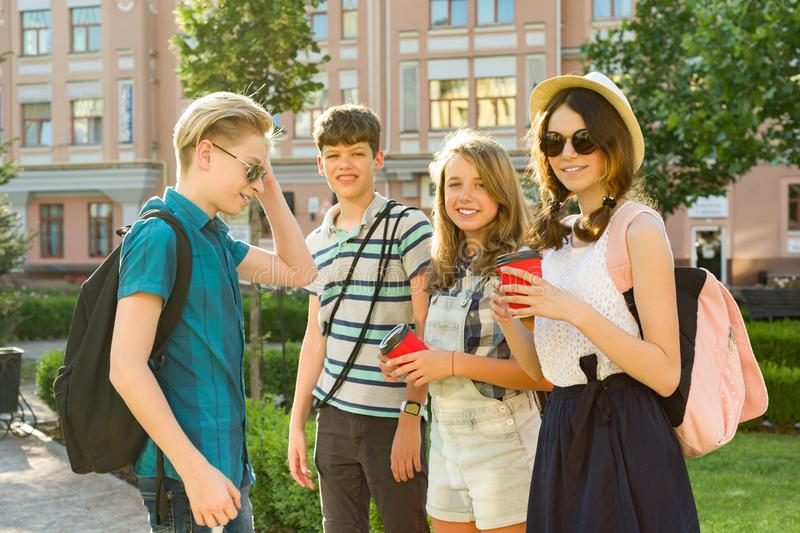 Group of happy teenagers 13, 14 years walking along the city street, friends greet each other at a meeting. Friendship and people concept stock image