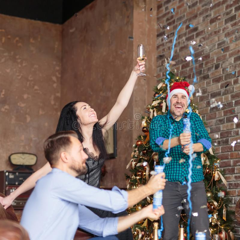 Group of happy three friends having fun with confetti and champagne at New Year`s party stock image