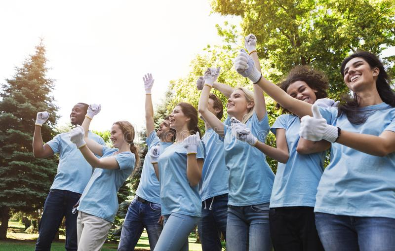 Group of happy volunteers celebrating success up in park royalty free stock photos