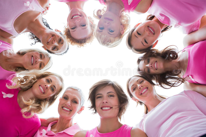 Group of happy women in circle wearing pink for breast cancer royalty free stock photo