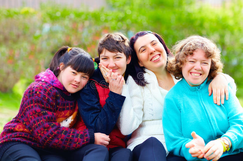 Group of happy women with disability having fun in spring park. Portrait of happy women with disability having fun in spring park stock photo