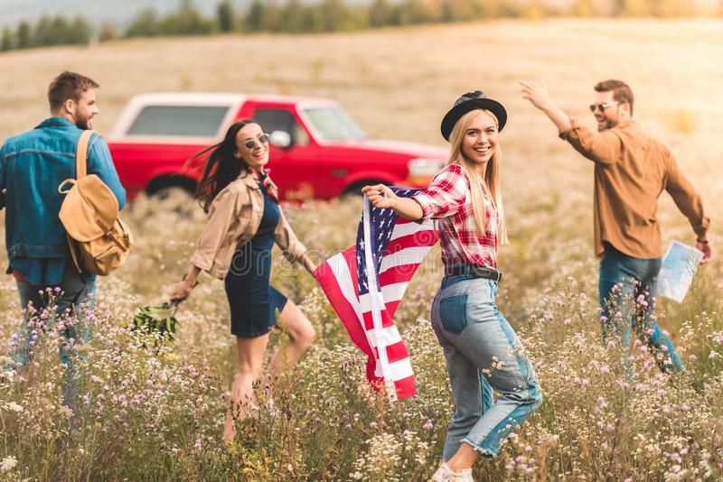 Group of happy young american car travellers with flag walking. By flower field royalty free stock image