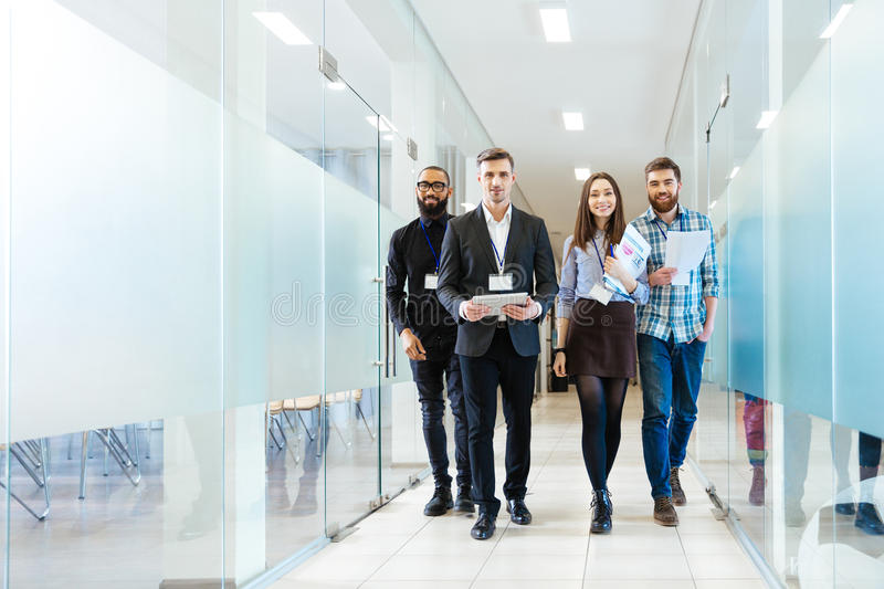 Group of happy young business people walking in office together. Full length of group of happy young business people walking the corridor in office together stock photos