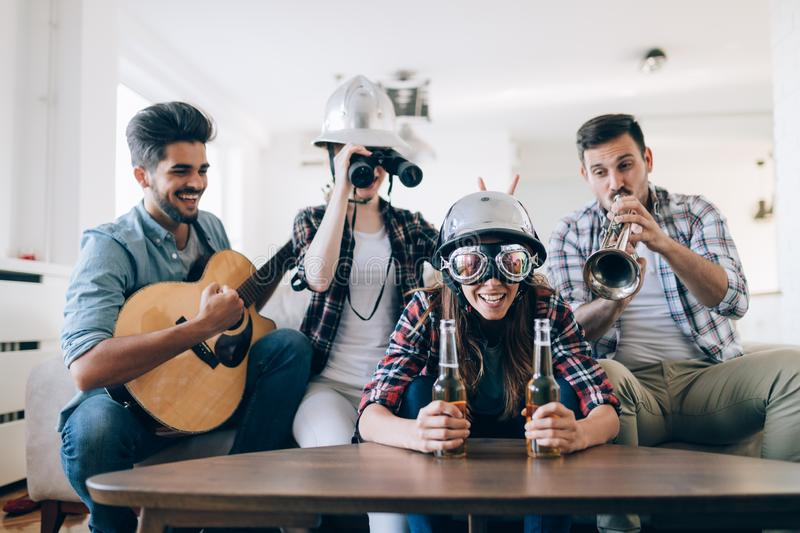 Group of happy young friends having fun and drinking beer. At home stock photography