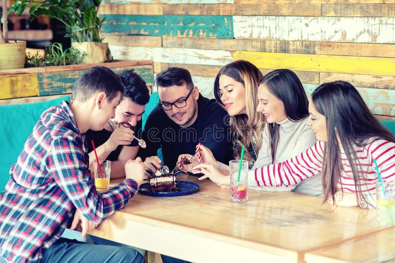 Group of happy young friends sharing and eating dessert cake at cafe table royalty free stock photo