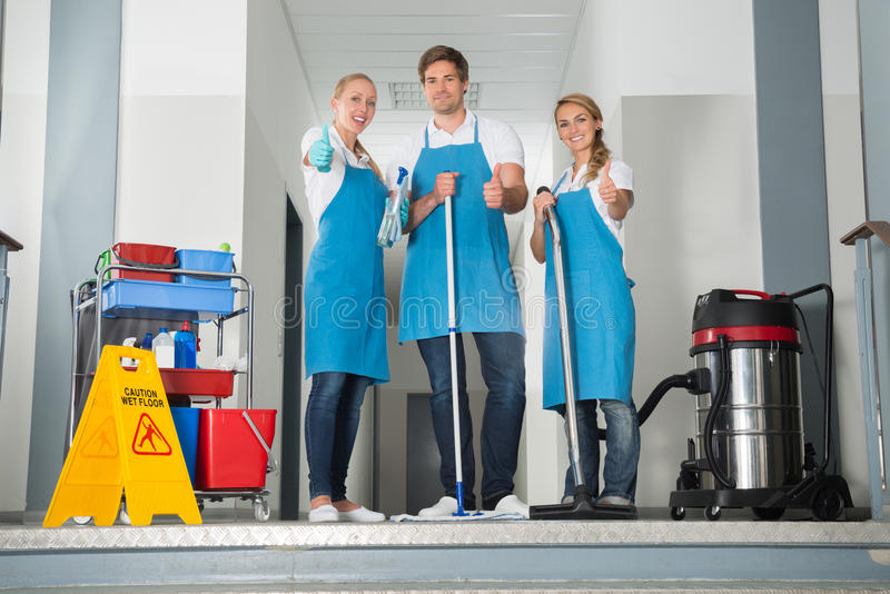 Group Of Happy Young Janitor Showing Thumbs Up royalty free stock images