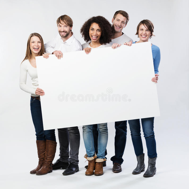 Group of happy young people with a blank sign stock images