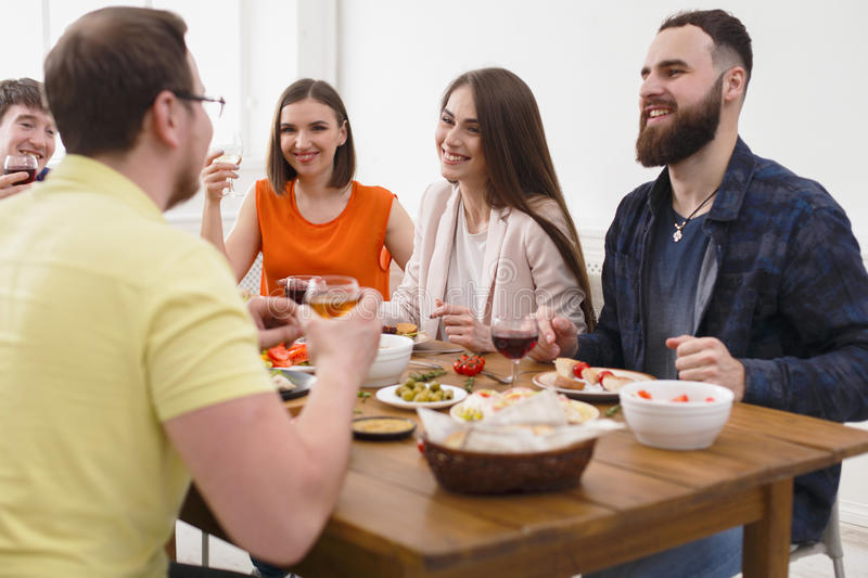 Group of happy young people at dinner table, friends party. Group of happy young people laugh and chat at dinner table, party for friends indoors at cafe or home stock images