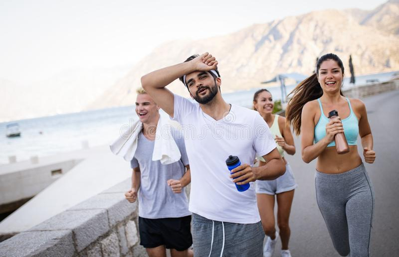 Group of young people friends running outdoors at seaside royalty free stock photos