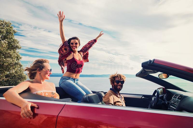 Group of happy people in red convertible car. stock photography