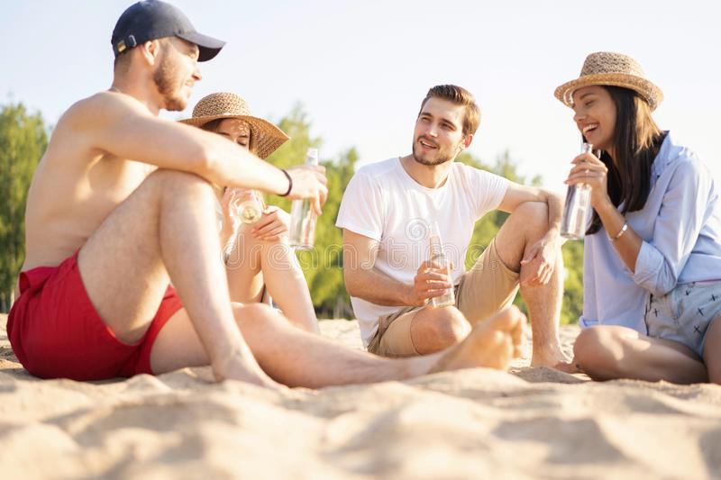 Group of happy young people sitting together at the beach talking and drinking beers stock photography