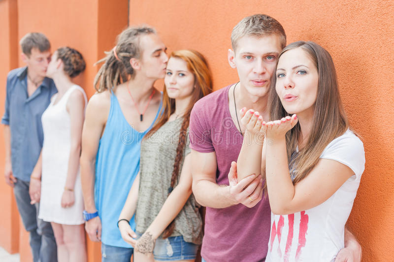 Group of happy young people standing near wall and kissing royalty free stock image