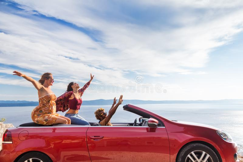 Group of happy people in red convertible car. royalty free stock photo