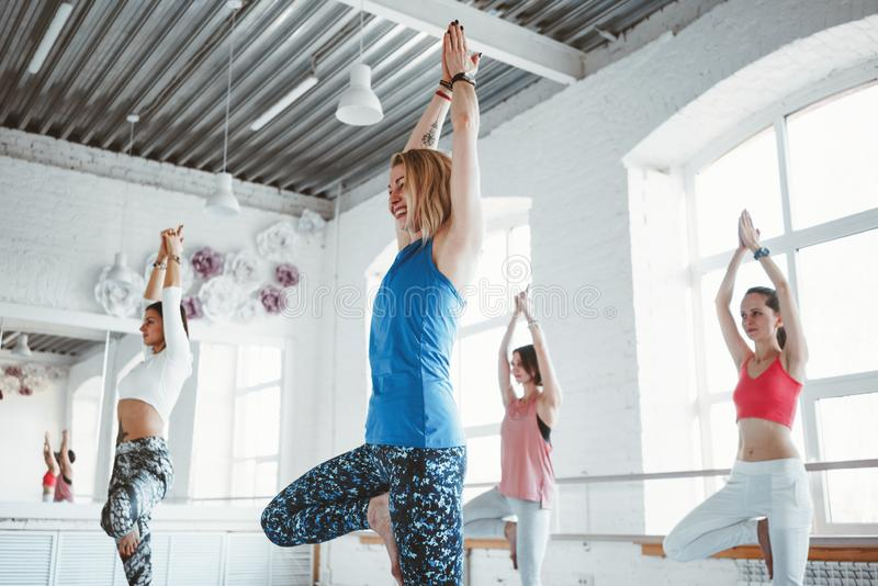 Group of healthy woman training together and doing fit exercise in white gym. People practice yoga poses together indoor. Group of healthy women training stock photos