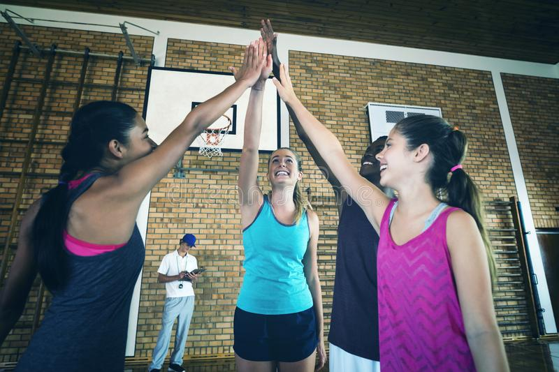 Group of high school kids giving high five in the basketball court royalty free stock image