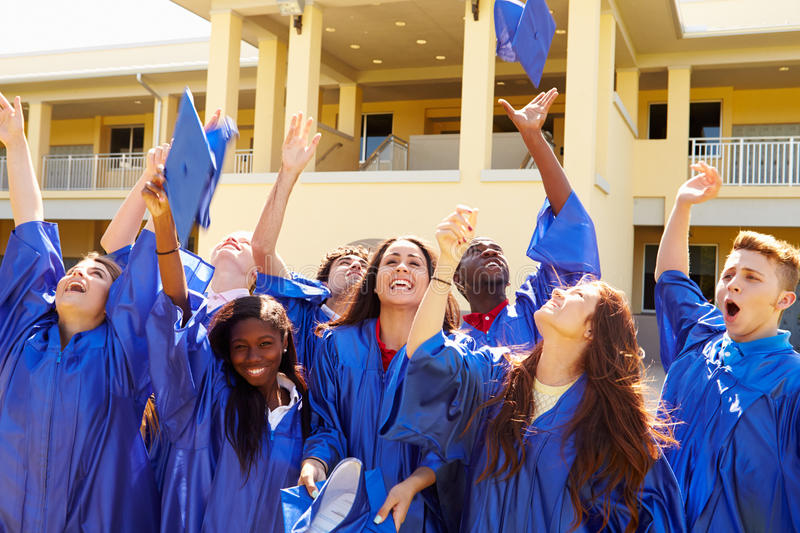 Group Of High School Students Celebrating Graduation. Throwing Mortars In The Air Cheering stock image