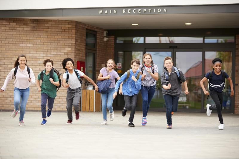 Group Of High School Students Running Out Of School Buildings Towards Camera At The End Of Class royalty free stock photos